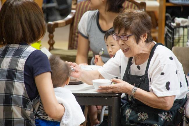 赤ちゃんに離乳食を与える認知症のおばあちゃん