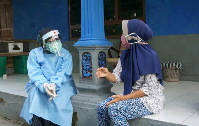 コロナ禍で精神不安定となった女性に救急処置を施す赤十字ボランティア (ジョグジャカルタ州、2020年8月)(C)インドネシア赤十字社