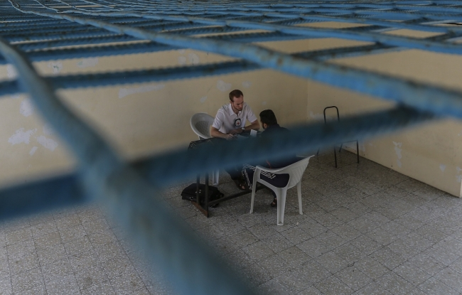 ガザにある収容施設で被拘束者と定期的に面会し、人道的な扱いを受けているかヒアリングを行うICRCスタッフ (C)ICRC
