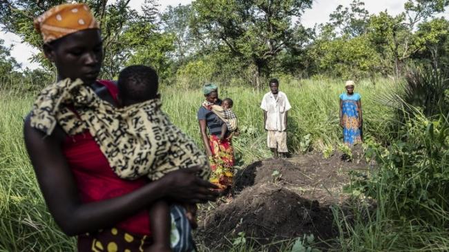 2019年3月に発生したサイクロンで亡くなった身内の墓参りに訪れる家族。犠牲者は納体袋に納められ集団墓地に埋葬された(モザンビーク) (C)ICRC