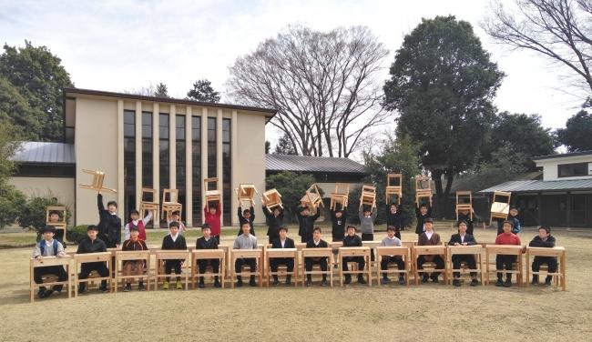 製作した机と椅子と写る2017年度の中等科1年生。今年の新入生は椅子は製作済み。机は今後作る予定。