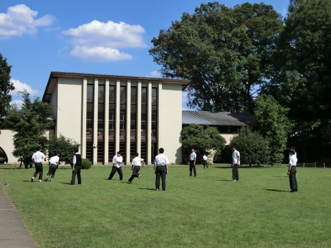 自由学園男子部体育館(東京都選定歴史的建造物)前の芝生で昼食後の休み時間のひとときを過ごす男子部の生徒