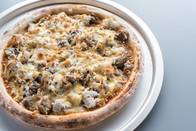 ▶もっこす鶏の炭火焼ドリアピザ ¥1,300   使用食材:もっこす鶏(マツヤマエッグファーム)、     味噌だれ(株式会社 内田物産(卑弥呼醤院))     燻製ナッツ・チーズ(燻製工房縁)など