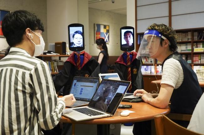 リアル参加とアバター参加の学生が混在するグループワークで個別フィードバックを行う谷中修吾教授(写真右)