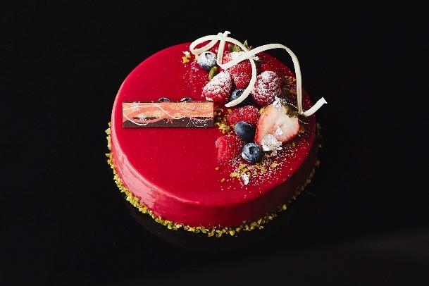 「Rouge Noël(ルージュ ノエル)¥5,400(税込)」赤い果実を使用した真紅のグラサージュ。中にはフランボワーズのムースとピスタチオのムースでクリスマスカラーをイメージ。果実の酸味とピスタチオの濃厚さを感じる、華やかなケーキ。