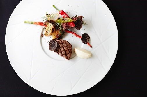 「京都産和牛フィレ肉 グリル 農園の野菜」 京都産和牛のフィレ肉をグリル焼きにし、マデラ酒から作った黒トリュフのソースでお召し上がりいただく、贅沢な一皿。