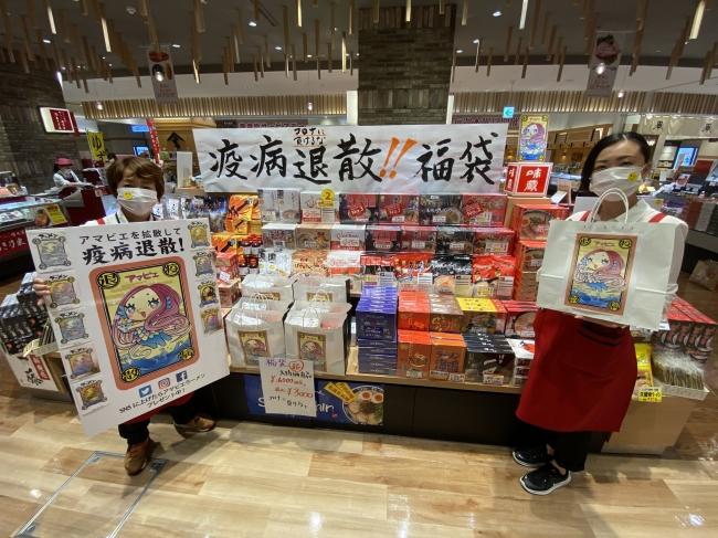 アマビエパネルを持つ橋川店長(左)福袋を手にする小野副店長(右)