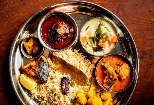 写真左の小さい銀の器から、レモンアチャール、マトンカレー、ココナッツシチュー、メカジキの南インド風カレー、カリフラワーのサブジ、プラオ(スパイス炊き込みご飯)、ブリのマサラ焼き。作り方はすべて本書に掲載しています。