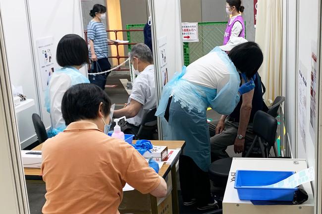 作業の迅速化を図るため、1つのワクチン接種エリアに2名の被接種者が衝立を挟んで入室