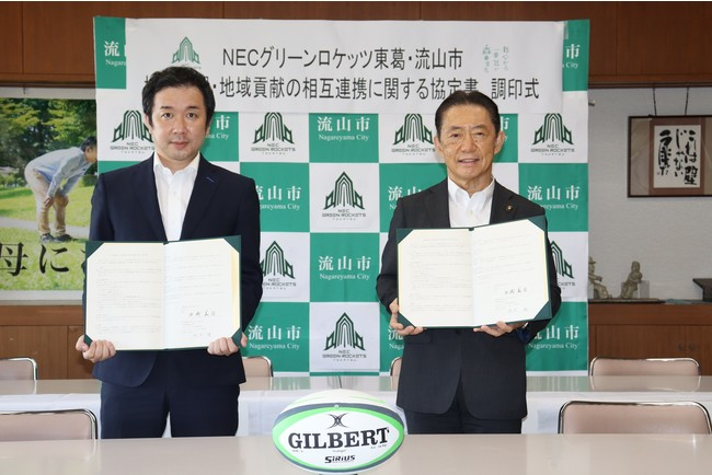 調印書を交わす梶原代表(左)と井崎市長(右)