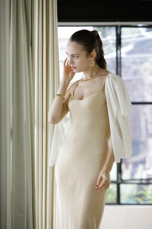 ワンピース(ホワイト)のウェストをカットし、前身頃を切り開いてカーディガンとして着用するイメージ。ドレスの上に軽く羽織ってパーティへの参加も可能。