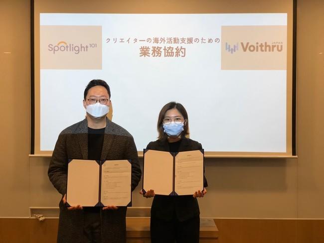 スポットライト101のキム・ヨンジョン代表(左側)とボイスルジャパンのパク・ジウン代表(右側)が業務提携契約書を持って記念写真を撮っている。