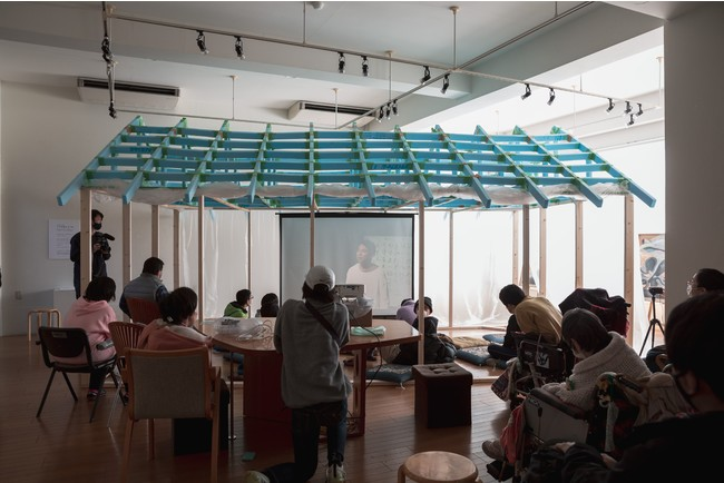 HANAのギャラリースペースに設置された小屋の中にスクリーンを置いて作品を上映。 作品「僕がうまれた日」たんぽぽの家アートセンターHANA 撮影:衣笠名津美