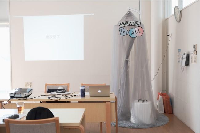 部屋の隅にテントを吊るして、タブレットとネックスピ ーカーを用意した個人視聴ブース。撮影:衣笠名津美