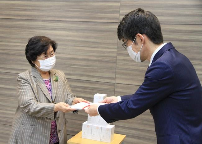 ▲健康家族 藤雄氏副社長から南風病院 貞方洋子理事長へ目録を手渡す