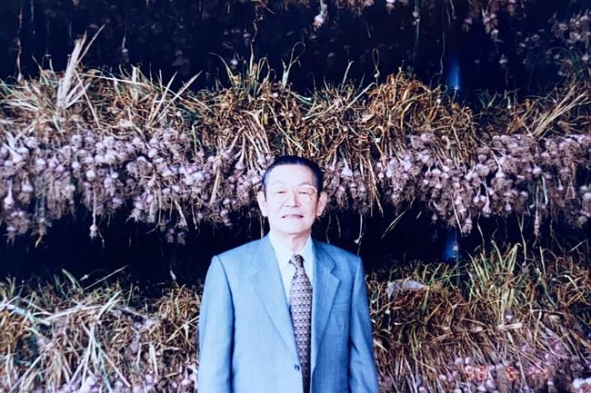 乾燥中のにんにくの前で。創業者・本多荘輔