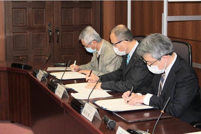 協定書に調印する稲垣病院長(写真奥)、小林笠岡市長(中央)、淺沼医学部長
