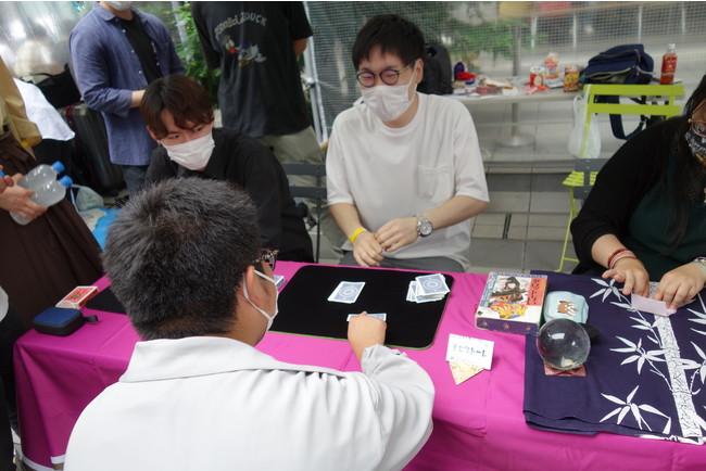 カードマジックを楽しむ参加者と学生