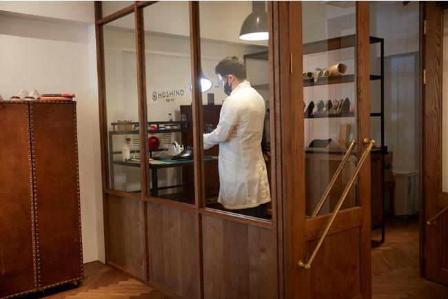 店舗奥の作業台ではラボコート(白衣)を着用した職人がパティーヌ染めや靴磨きを行う