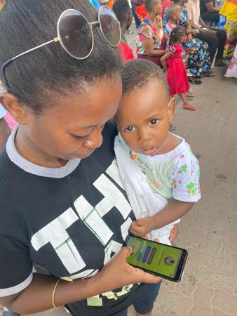 バス停にて、アプリを確認する妊婦