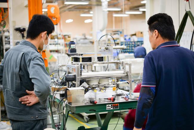 丸め機の開発中の工場長橋本(右)脇(左)