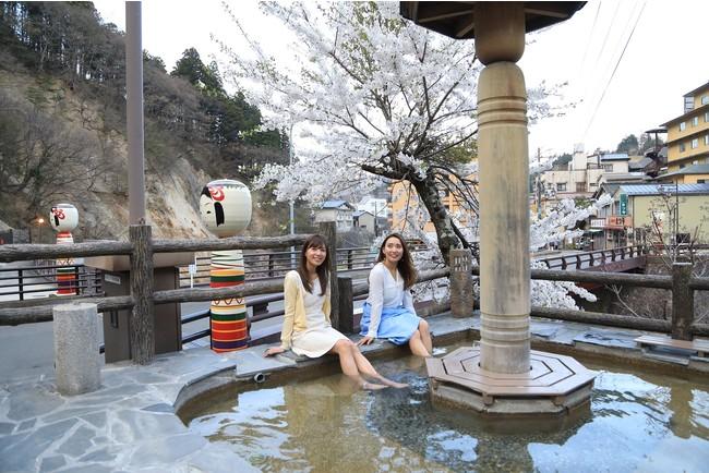 女性客が温泉街を楽しむ光景