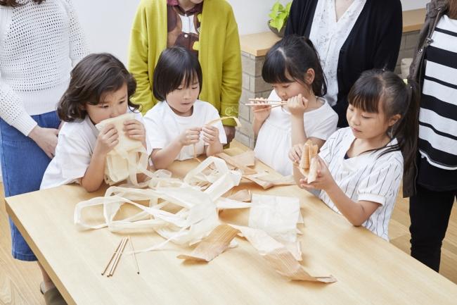 """子供たちがカンナ削りの""""木のストロー""""を五感で楽しむ様子"""