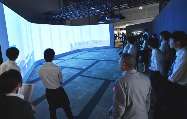【写真】3面の大型スクリーンに映し出される展示場