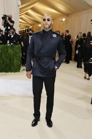 スウィズ・ビーツは、メンズコレクションから、ネイビーのベルトジャケットにブラックのウールパンツ、ブローチ、ブラックのパテントダービーに身を包み登場。(C)Getty