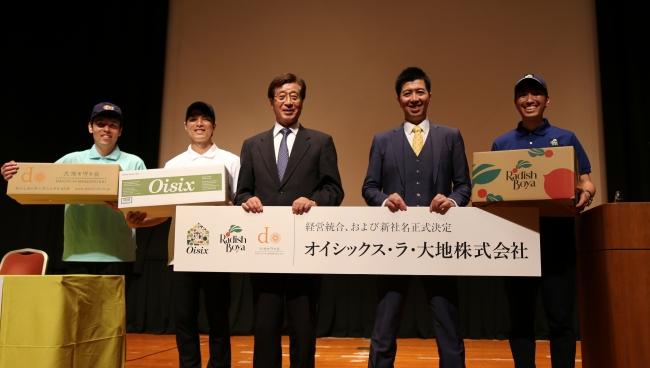 新社名のパネルをもつ当社会長の藤田和芳(左)と社長の高島宏平(右)